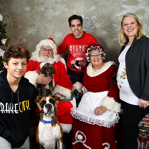A photo of Mike's family with Santa and Mrs. Claus.